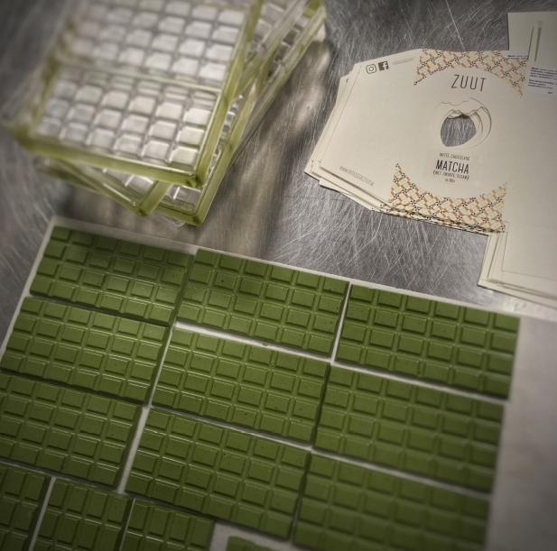 Bij Chocolaterie Zuut bieden ze matcharepen aan. In deze groengekleurde repen wordt de matcha gecombineerd met witte chocolade en zwarte sesam