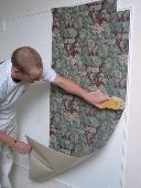 Etalez la bande contre le mur avec une brosse à tapisser, toujours de haut en bas