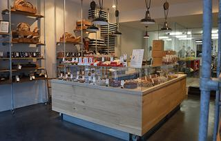 De winkel is zeer open ingericht, met een centrale toonbank waar je volledig rond kunt, en een open atelier achteraan in de winkel