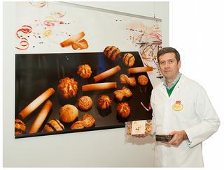 Productiemanager Geert Vandoorne met enkele verpakte eindproducten van Poppies: twists en kaneelvlinders in trays en zakken