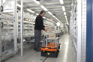 Deze AGV volgt een magneetstrip op de vloer en krijgt onderweg opdrachten via de vloermarkeringen naast de tape