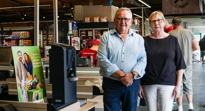 Michel en Nadine Ronse van Intermarché Doornik poseren trots naast het nieuwe, gesloten kasverwerkingssysteem