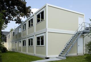 Containerunits gestapeld in twee verdiepingen met verdiepingstrap