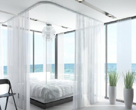 Het gordijnsysteem aan de ramen zit verwerkt in een uitsparing van het vals plafond. Voor de gordijnen rond het bed heeft men het systeem in opbouw geplaatst