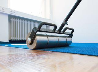 Nadat de nieuwe vloerbedekking – hier een tapijt – middels de verwijderbare lijm gefixeerd is op de ondergrond, wordt die nog even aangewalst